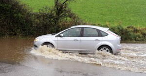 A car makes it's way through the flooded road outside Clonakilty, Co. Cork yesterday. Photo: Billy macGill