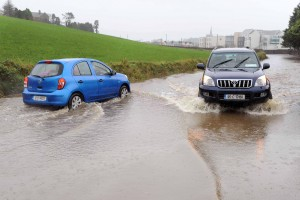 Two cars carefully pass each other on a flooded road outside Clonakilty, Co. Cork yesterday. Photo: Billy macGill